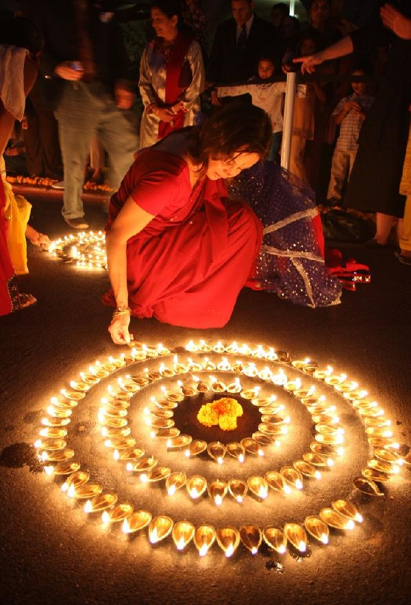 Indian Lady Creating Diwali with lamps.
