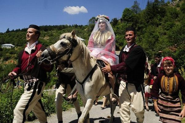 Bride Dafina Grozdanovska rides a horse to meet the groom dressed in folk costume in a traditional wedding ceremony in the village of Galicnik