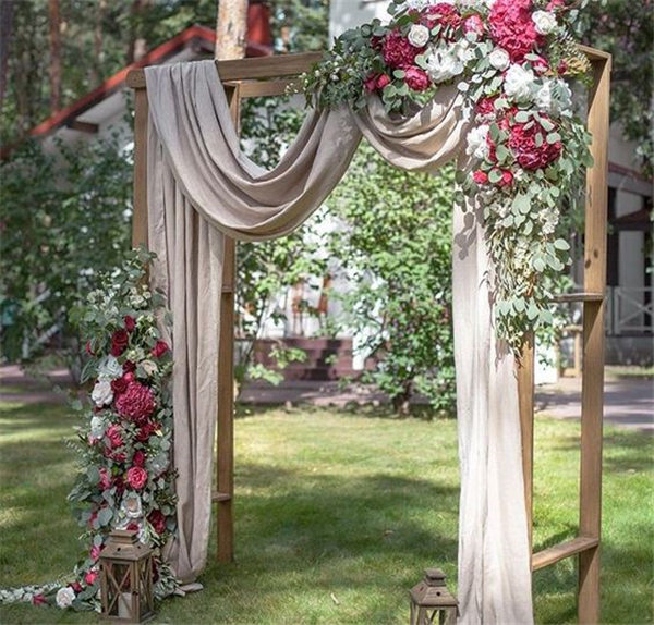 Beautiful-wedding-ceremony-backdrop-arbor-with-draping-flowers-and-lantern-accents